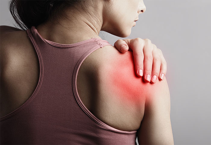 Young strong sporty woman suffering from pain in shoulder in sport wear. Touching the hand. Sports exercising injury. Closeup portrait with highlighted in red and empty copy space. Back view. The concept of medicine, massage, physiotherapy.